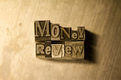"Money review - Metal letterpress lettering sign. Lead metal ""Money review"" typography text on wooden background Royalty Free Stock Images"