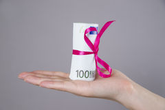 Money with ribbon in female hand on a gray background Stock Images