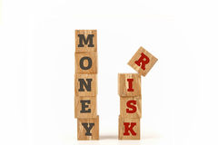 Money and Risk word written on cube shape. Money and Risk word written on cube shape wooden surface isolated on white background Stock Photos