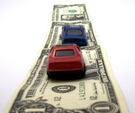 Money Road. Toy cars over a road made of bills Royalty Free Stock Image