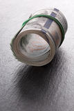 Money roll dollars on a slate table Royalty Free Stock Photos