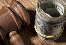 Money roll and judges hammer on wooden table close up. Top view stock photography
