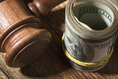 Money roll and judges hammer on wooden table. Top view royalty free stock image