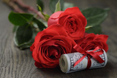 Money roll with rose flower. On wooden table Stock Photo
