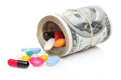 Money rolled up with pills flowing out Stock Photography