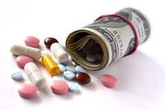 Money rolled up with pills flowing Royalty Free Stock Image