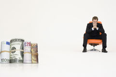 Money rolls with pensive businessman on chair representing financial problems Royalty Free Stock Photography