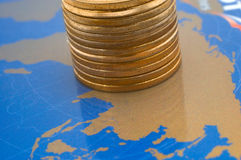 Money rule the world. Stack of shiny coins over world map on plastic card royalty free stock images
