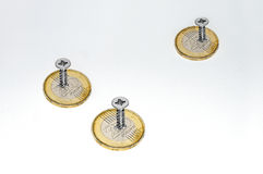 Money at safe place. Three coins on a table fixed with screws, to be at a safe place Royalty Free Stock Photo