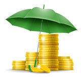 Money safety concept. Four stacks of golden coins under an green umbrella Royalty Free Stock Photo
