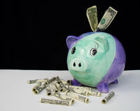 Money Saved. Piggy Bank on Black background with money everywhere around it - concept: saving money Royalty Free Stock Photo