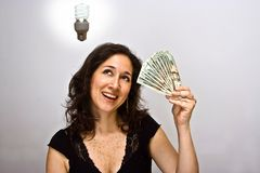 Money saver. Woman with a money saving idea, and a compact fluorescent light bulb royalty free stock image