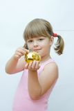 Money saving. Cute, little girl with golden piggy bank Royalty Free Stock Image