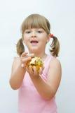 Money saving. Cute, little girl with golden piggy bank Royalty Free Stock Photos