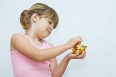 Money saving. Cute, little girl with golden piggy bank Royalty Free Stock Photo