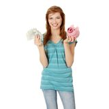 Money saving. Happy teen holding a piggy bank and dollars, isolated on white background Stock Photos