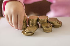 Money saving. Children's hand holding a stack of coins Stock Photos