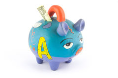 Money saving in a colorful piggy bank. Isolated on white background Stock Image