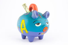 Money saving in a colorful piggy bank. Isolated on white background Royalty Free Stock Photos