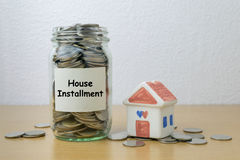 Money saving for house installment in the glass bottle Stock Photos