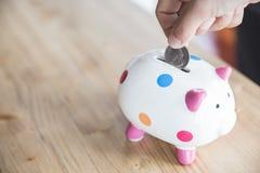 Saving coin in piggy bank Royalty Free Stock Photos