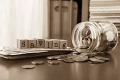Money saving word with coins and banknotes, Sepia toned Royalty Free Stock Photography