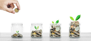 Money savings and business investment concept, bottle of coins on white wood on white background Stock Photo