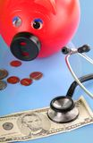 Money and savings not well. Piggy bank and stethoscope by money Royalty Free Stock Photos