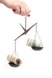 Money on scales unbalanced Royalty Free Stock Photography