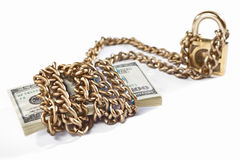 Money and security concept. Stack of 100 dollar bills with golden chain and padlock, concept for financial security royalty free stock image