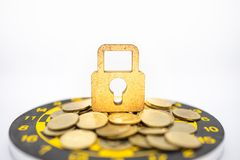 Money, Security, Target and Goal Concept. Close up of wooden master key lock icon on pile of gold coins on black and yellow dart. Board on white background royalty free stock photo