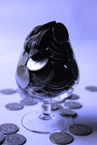 Money. In shape of coins spilling out of a transparent drinking glass. The picture can denote luxury, wealth, greed and success Royalty Free Stock Photography