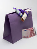 Money and shopping!!. A fifty euro note rolled on a shopping bag hold as a symbol of shoping Royalty Free Stock Photo