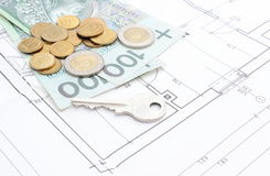 Money and silver key lying on the housing plan Stock Photos