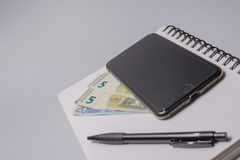 Money, smart phone, pen and notebook on the office table on white background. Budget concept. Money, smart phone, pen and notebook on the office table on white Royalty Free Stock Image