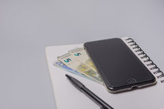 Money, smart phone, pen and notebook on the office table on white background. Budget concept. Money, smart phone, pen and notebook on the office table on white Stock Image