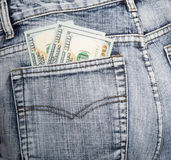 Money, some notes on hundred dollars, in a hip-pocket of blue je. Ans. Close up Royalty Free Stock Photo