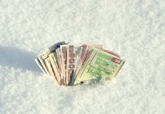 Money of south-east Asia in the snow in the winter. Currency of Hong Kong, Indonesia, Malaysia, China, Thai. Royalty Free Stock Image