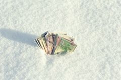 Money of south-east Asia in the snow in the winter. Currency of Hong Kong, Indonesia, Malaysia, China, Thai. Stock Images