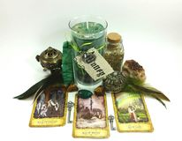 Money Spell Candle. This is a spell candle used to attract money and prosperity. It has a white background with tarot cards, feathers, crystals, keys, stones and Stock Photos