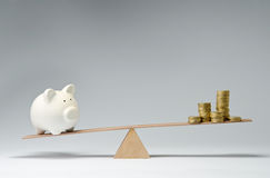 Money spendings against money savings. Money coins and piggy bank balancing on a seesaw Stock Photo