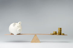 Money spendings against money savings. Money coins and piggy bank balancing on a seesaw Royalty Free Stock Photography