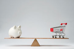 Money spendings against money savings. Shopping trolley and piggy bank balancing on a seesaw Royalty Free Stock Photography