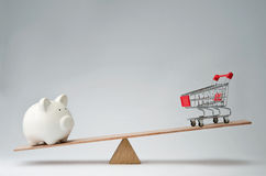 Money spendings against money savings. Shopping trolley and piggy bank balancing on a seesaw Royalty Free Stock Images