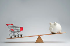 Money spendings against money savings. Shopping trolley and piggy bank balancing on a seesaw Stock Images