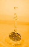 Money splash. A euro coin drops into a gold liquid Royalty Free Stock Photos
