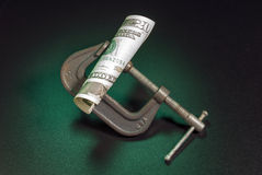 Money squeeze. As a metaphor for inflation and increase in taxes Stock Image