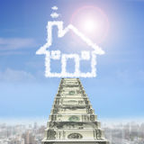 Money stairs toward house shape white cloud. In blue sky background Stock Photo