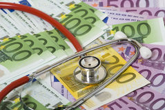 Money and stethoscope. Lot of paper money euro banknotes and red stethoscope Royalty Free Stock Photos