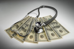 The cost of healthcare. Money and stethoscope to illustrate the cost of health care Stock Photos